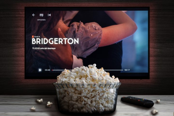 """Cali, Colombia - February 9 2021: Netflix app on tv screen playing """"Bridgerton"""" behind a bowl of popcorn and a remote control."""